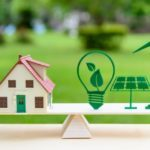 Future clean / renewable or alternative energy for modern living concept : House model, light bulb with green leaf, solar panel, wind mill on wood balance scale, depicts the awareness of environment. (Future clean / renewable or alternative energy for